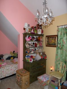 Girls room with vintage kitchen cupboard filled with international doll collection and vintage snow white print