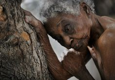 'The Elderly': Idamise Pierre leans against a tree, her withered skin resembling its bark, as she waits to bathe at the Azil Communal Home for the Aging. With weary resignation, the elderly have endured decades of Haiti's poverty and political turmoil and in their twilight years are now left with heavy hearts by the earthquake that eternally altered their lives. photograph taken by Nikki Kahn