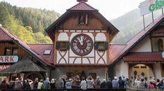 Touristen in Triberg versammeln sich vor der größten Kuckucksuhr weltweit, um zur vollen Stunde den Kuckuck nicht zu verpassen.