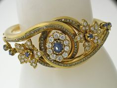 Victorian Sapphire & Diamond Bangle Victorian Sapphire  Diamond Bangle Bracelet, Circa 1890~Stunnning!! This Victorian bracelet is incredibly well-preserved. It has a center Lady Di Sapphire look with an oval sapphire a liitle over one carat. The sapphire is Burma, no heat. It is surrounded by old mine diamonds weighing approximately 2.00cts. There are two sapphire and diamond flourets set offset the center piece. The design is French.