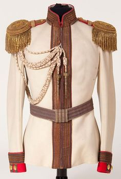 Imperial Russian Horse Guard Regiment officer's tunic or 'Koller', circa 1900.  White boiled wool tunic with red cuffs and piping. Silver bullion braid mixed with orange and bordered in blue trim on collar, front and cuffs. Collar and cuffs also display silver bullion Litzen, those on the cuffs with gold double-headed eagle buttons. Complete with gold bullion fringed epaulettes faced in red with applied gold tone crown and cipher of Nicholas II.