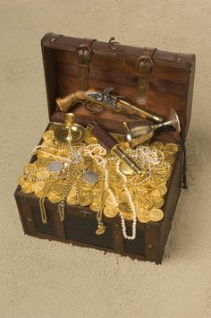 Photo about Pirate treasure chest with the lid open brimming with gold coings and pirate paraphernalia on a sandy beach. Image of pistol, jewelry, booty - 15246990 Pirate Art, Pirate Life, Things To Do When Bored, Cool Things To Buy, Sibling Birthday Parties, Dragon Cave, Pirate Treasure Chest, Money Pictures, Gold Money