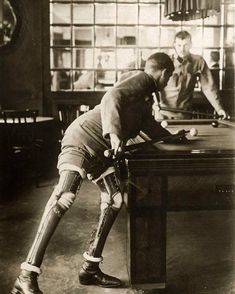 World War I soldier, a double amputee, plays billiards with prosthetic legs, 1915.