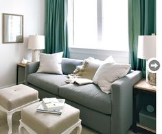Grey couch, beige footrest, green curtains