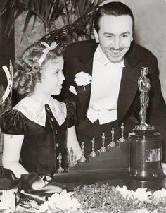 """Walt Disney, un genio de la animación, mirando el premio Oscar honorífico, por la película """"Blanca Nieves y los Siete enanos"""""""