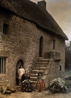 A woman and two children sit in front of their thatch-roofed longhouse with outside stair, Auray, Morbihan, 1929.    Brittany