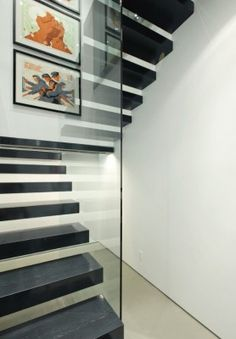 Straight timber staircase with central glass screen forming balustrade. Via Dyna Contracting