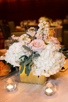 Champagne, blush, and ivory centerpieces in gold cube vases.  Reception at the Four Seasons.  White hydrangea, champagne roses, peach stock, blush tones. Flowers by Sisters Floral Design Studio www.sistersflowers.net  Image by L Photographie