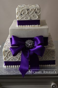Deep Purple Elegance #13Bow This three-tier square design cake is a great size for most weddings. Each layer is wrapped in satin ribbon, then accented with a beautiful bow and brooch. Toppers can be added, but are brought in by the bride and groom.