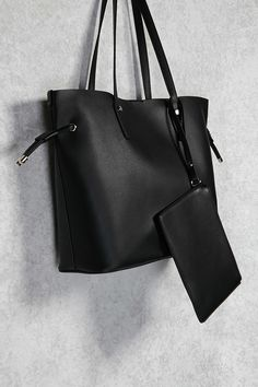 A tote bag crafted in a smooth faux leather, complete with dual shoulder straps, tassel pulls at the sides, a top magnetic snap closure, and an attached mini zipper wallet.