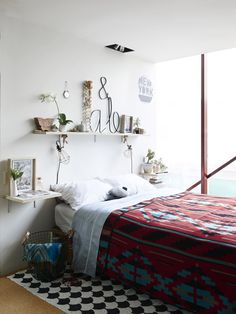 Amber and Ben's bedroom. 'I like to buy blankets on my travels, this one is from The Navajo Indian Reservation better known as Monument Valley' says Amber. Sheets and pillowcases by Hunting for George, blanket in basket on the floor from Nepal, shell necklaces from a childhood trip to Fiji. Alphabet signs and wire baskets from The Woodsfolk. The eye cushy on the bed by local maker Made By Mosey. Photo – Eve Wilson, production – Lucy Feagins / The Design Files.