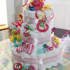 Cute diaper cake for a baby girl baby shower! What a unique way to give some essential gifts!