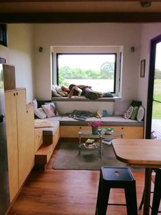 The tiny house living room has a cozy reading nook pop-out and an L-shaped couch. The tiny house living room has a cozy reading nook pop-out and an L-shaped couch with storage underneath.