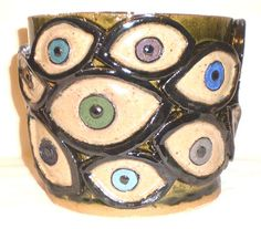 This is a stoneware hand-built slab/coil pot with twenty molded eyes of various colors. This unique piece of pottery would be an ideal gift for someone whose tastes tend towards the bizarre.