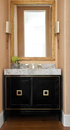 Chic gold and black powder room is fitted with a stunning gold and black washstand completed with a marble countertop and a polished brass faucet fixed in front of a marble backsplash.