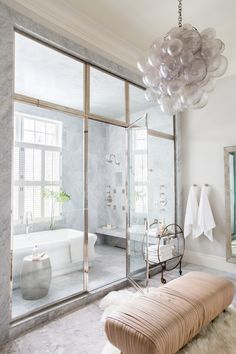 Enclosed bath and shower all in one in this stunning marbled master ensuite Design by Alice Lane Interiors