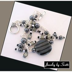 A hand-painted gray Kazuri bead with black stripes is the centerpiece for this unique, elegant handmade bracelet. Hematite (Alaska Black Diamond) 8mm rounds sit on either side of the Kazuri bead, alon