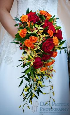 Red, orange and white roses with yellow orchids in a cascading bridal bouquet.