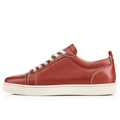 """Taking his classic lowtop shape to luxurious new heights is """"Louis Junior."""" In this season's dark and handsome terre cuite, this red soled sneaker gets you from A to B in unmistakable Louboutin style."""