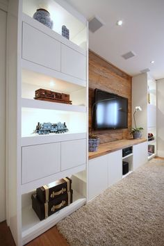Built-in Apartment TV wall: smooth white cabinets with rustic wood insert feature wall