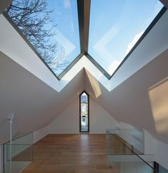 A narrow window extends up to the roof of this chapel-like wooden house in southwest London: