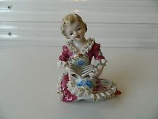 JAPAN*VINTAGE*PORCELAIN GIRL SITTING ON HER KNEES*READING A BOOK*FIGURINE*.  I have one like this, but her dress is blue.
