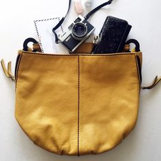 Mustard Yellow Leather Shoulder Bag Highlights • Plinio Visona • Genuine Leather • Magnetic closure • Wooden Rings • Pre-loved • Brown stitching detail • Side zippers Plinio Visona Bags Shoulder Bags