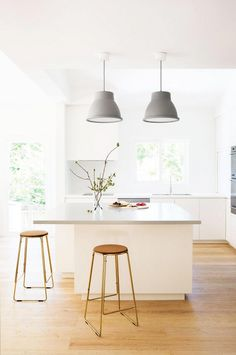 Bright and airy kitchen with gray pendant lights, simple countertops, and modern bar stools