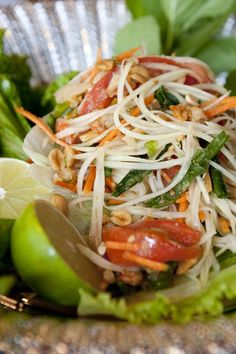"NYT Cooking: In Isan (and the rest of Thailand), green papaya salad is called som tum, with ""som"" meaning ""sour"" and ""tum"" referring to the pounding sound of the large pestle used to crush ingredients. It is eaten by itself as a snack, or with marinated grilled beef and chicken."