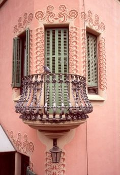Pink building; green shutters; purple balcony photo