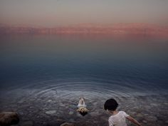 Floating on dreams and whispers, girls from a West Bank village cool off in the salt-laden waters of the Dead Sea. With its main tributary, the Jordan, at less than a tenth of its former volume, the inland sea has dropped some 70 feet since 1978.
