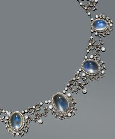 Silver, gold, moonstone and diamond necklace, early 1900s.  A very decorative necklace in 'garland-style' set with 14 oval moonstone cabochons, each set within a garland frame set with diamonds, interconnected by a diamond-set ribbon link, mounted in silver topped gold. #antique