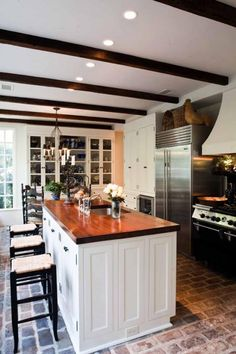 Farmhouse kitchen, brick floors, butcher block island, baskets, exposed beams...