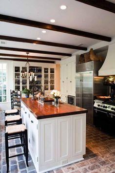 Farmhouse kitchen, brick floors, butcher block island, baskets, exposed beams...