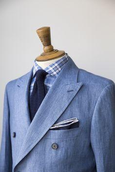 Light blue double-breasted linen jacket, light blue plaid shirt, navy knit tie