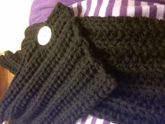 Black neck warmer with button. This is a double stranded scarf that has a button that holds the scarf in place for the neck warmer look.