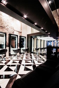 The decor of this modern elegant beauty salon creates a sense of luxury through the use of black and white tile patterns.  The interior design is sophisticated with its use of bronze sheer curtains to create private treatment rooms. Other decor ideas are the use of sleek styling stations giving a boutique hair salon ambiance. | #geometric | #style | #fashion |