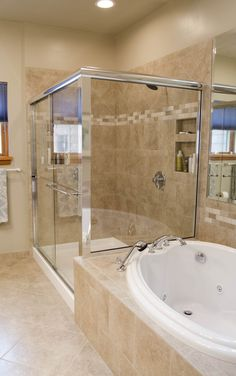 This stand up, all glass shower makes this bathroom look bigger, while the backsplash on the shower carries over into the spacious garden tub.