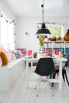 White dining room with bright accent colours - really like the window bench seating too and the low pendant lighting over the table