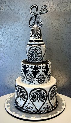 Tiered cake with black and white, intricately detailed design.