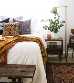 Beautiful bedroom, wooden bench, target lamp, white jug, plant, vintage fabric cushions and rug
