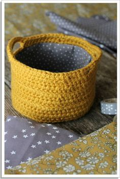 I like the idea of lining a crocheted basket with fabric.  This site is not in English.