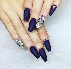 Matte dark blue nail art design. The stark contrast between the sharp matte nail polish with the eccentric and colorful design filled with embellishments is what makes this nail art truly beautiful and unique.