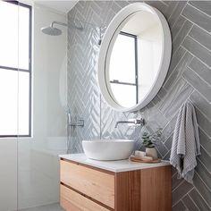 Coastal Home Interior Grey herringbone subway tile on modern bathroom with floating vanity, white vessel sink and round mirror Bathroom Renos, Laundry In Bathroom, Bathroom Renovations, Small Bathroom, Mirror Bathroom, Modern White Bathroom, Master Bathrooms, Bathroom Colors, Bathroom Cabinets