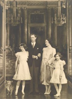The Royal Family, including Dookie, at Buckingham Palace, 20 December 1938   Royal Collection Trust Photograph of a full length group portrait of the Royal Family taken in Buckingham Palace with (from left to right): Dookie the corgi, Princess Elizabeth (b. 1926) now HM Queen Elizabeth II, King George VI (1895-1952), Queen Elizabeth (1900-2002) and Princess Margaret (1930-2002).