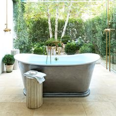 Freestanding metal bathtub with antique stone stool, floor to ceiling windows and gorgeous view of greenery