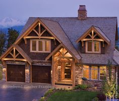 Wood shingling combined with natural slate rock makes this home look enchanting illuminated at its ridges at dusk, just a few options to make your mountain style home stand out.