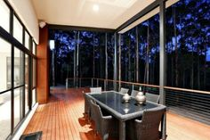 The timber decking alfresco area at night. This shot also shows the timber cladding on the back of the chimney. Notice the surrounding bushland - a wonderful retreat.