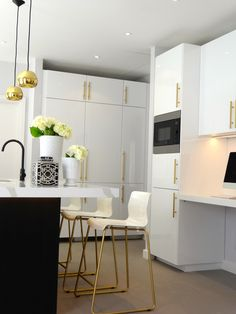 Black & white kitchen with brass and gold accessories, high gloss cabinets, gold brass pendant lights, kitchen island, greek key blinds, cream & gold bar stools. ikea hack. modern kitchen. grey stone tiles.