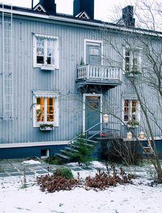 Kaksikerroksinen puutalo on neljän perheen koti. Vanhan syreenin oksille on ripustettu kirpputorilta löytyneitä lyhtyjä.